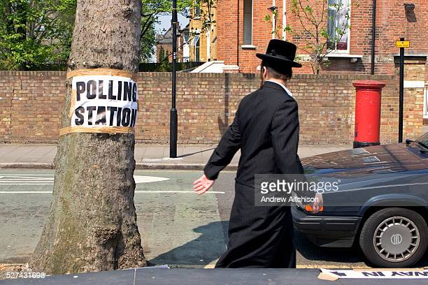 An Orthodox Jewish man walking down Portland Avenue past a Volvo and a sign for the local polling station taped to a tree The polling station for the...