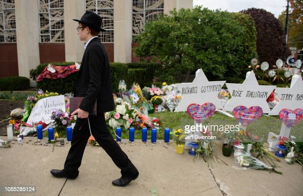 An orthodox jewish schoolboy passes a memorial for victims of the mass shooting that killed 11 people and wounded 6 at the Tree Of Life Synagogue on...
