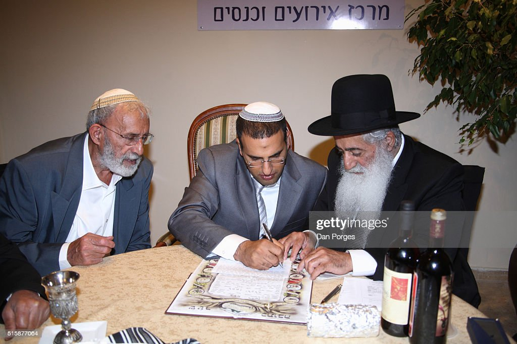 An Orthodox Jewish Wedding A Groom Center Signs The Ketubah Or Marriage