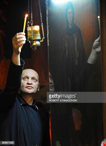 An Orthodox man lights candles at the Sveti Kliment Ohridski Cathedral in Skopje during the Good Friday processions on April 25 2008 The Orthodox...