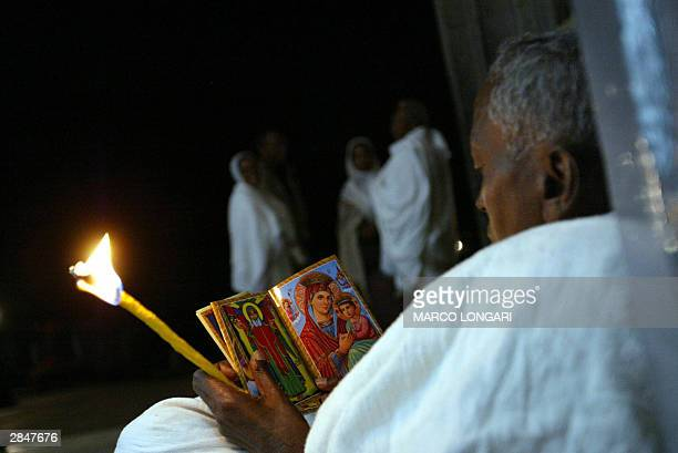 An orthodox man sits 06 January 2004 outside the Trinity Church in Addis Ababa Ethiopia praying over images of the Holy Virgin before joining the...