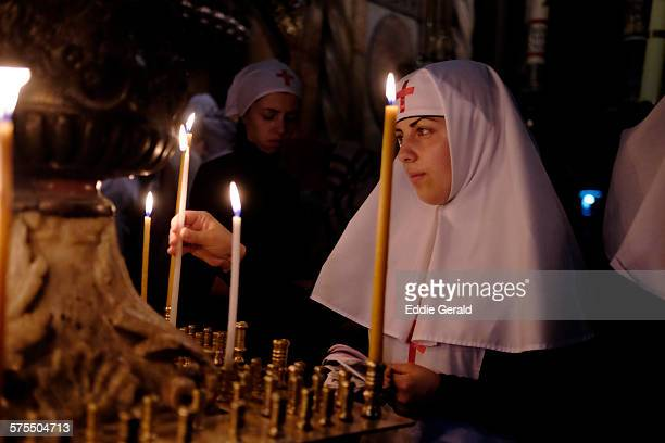 An orthodox nun lighting candles inside the Church of Holy Sepulchre Christian Quarter old city east Jerusalem Israel972
