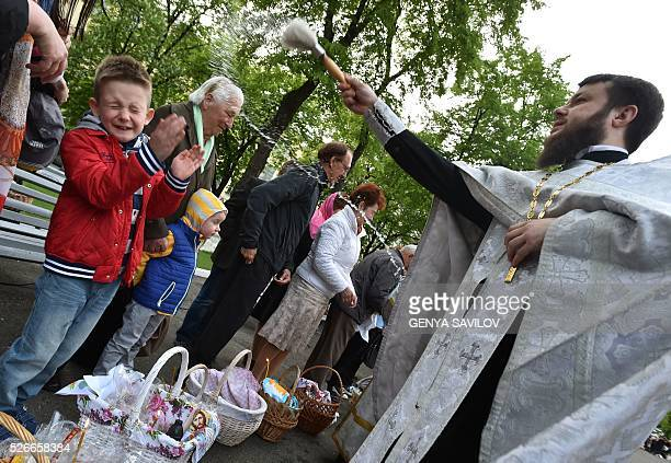 An Orthodox priest blesses believers and their traditional Easter cakes and painted eggs during an Orthodox Easter ceremony at the Volodymyrsky...
