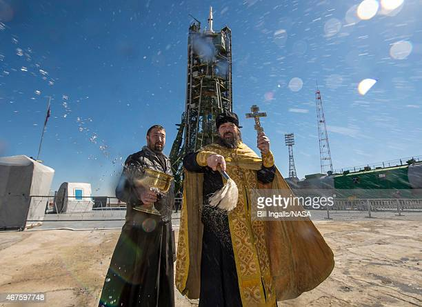 An Orthodox Priest blesses members of the media after he blessed the Soyuz rocket at the Baikonur Cosmodrome Launch pad March 26 2015 at the Baikonur...