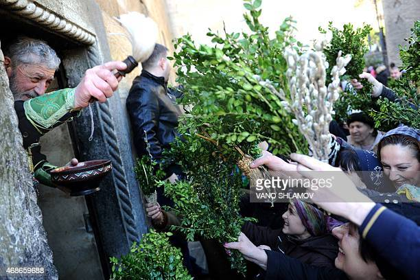 An Orthodox priest blesses worshippers during Easter Sunday in Tbilisi on April 5 2015 Palm Sunday marks the start of the week leading up to Easter...