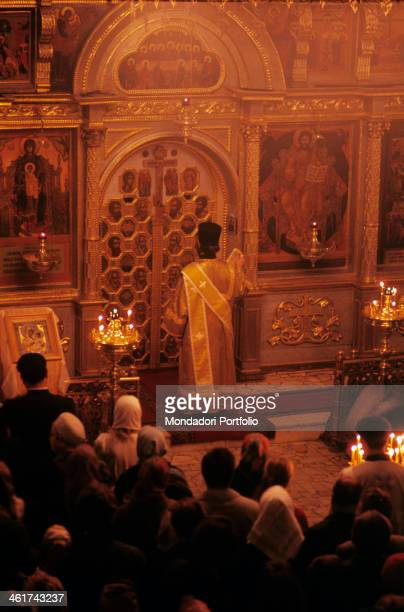 An orthodox priest facing the gilted iconostasis with the images of christian saints leads the liturgical rite under the eyes of many worshipers...
