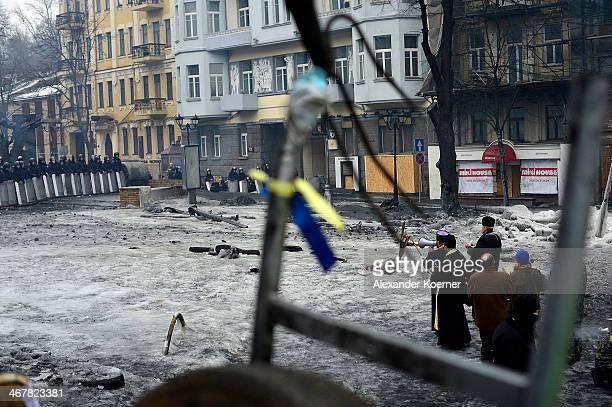 An orthodox priest holds a ceremony between riot police forces and a barriacde on Hrushevskoho Street on February 8 2014 in Kiev Ukraine Today about...