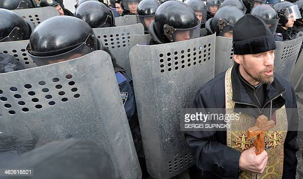 An Orthodox priest holds a cross in front of riot policemen standing guard in front of the parliament's building in Kiev on January 14 as Ukrainian...
