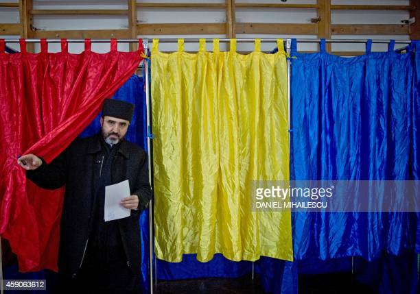An orthodox priest leaves a polling booth colored in Romanian national flag colors at a polling station in Bucharest city on November 16 2014 to...