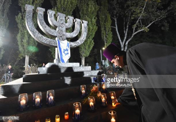 An Orthodox priest places a candle at the Menorah-shaped memorial dedicated to the victims of the Babi Yar massacre during the commemoration ceremony...