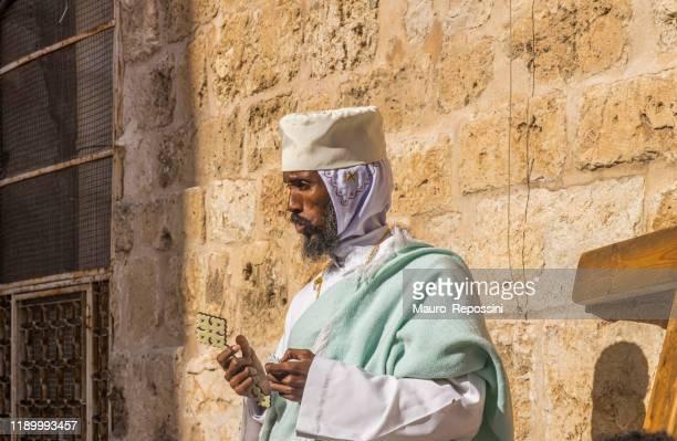 un prete ortodosso che prega nel cortile della chiesa del santo sepolcro nella città vecchia di gerusalemme, in israele. - chiesa del santo sepolcro foto e immagini stock