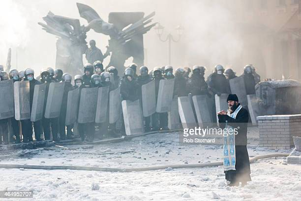 An Orthodox priest prays between police and protestors at the scene of antigovernment protests near Dynamo Stadium on January 25 2014 in Kiev Ukraine...