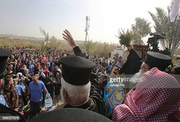 An Orthodox priest releases a pigeon during Epiphany celebration on January 22 2016 at the eastern bank of The River Jordan in Beit Aneya Jordan...