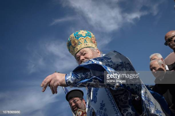 An Orthodox priest seen throwing a wooden crucifix into the sea during the annual Epiphany Day and the blessing of the waters celebrations in the...