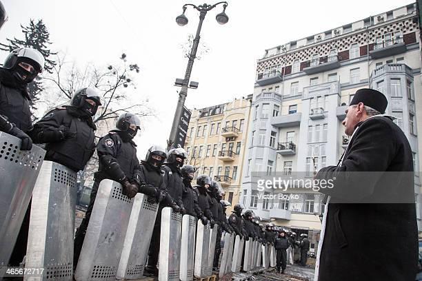 An Orthodox priest urges policemen not to use force against protesters on Grushevskogo Street on January 28 2014 in Kiev Ukraine President Viktor...