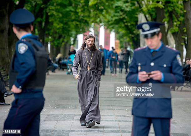 An Orthodox priest walks near guarding policemen in southern Ukranian city of Odessa on May 4 2014 Flowers candles and photos of the dead pile up...