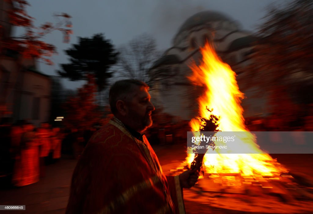 An Orthodox priest watches the ceremonial burning of dried oak branches, the Yule log symbol for the Orthodox Christmas Eve, in front of St. Sava Church on January 6, 2014 in Belgrade, Serbia. Most Orthodox Christians celebrate Christmas according to Julian Calendar on January 7.