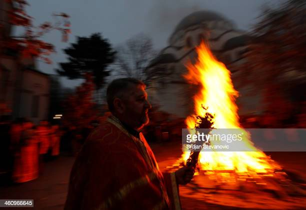 An Orthodox priest watches the ceremonial burning of dried oak branches the Yule log symbol for the Orthodox Christmas Eve in front of St Sava Church...