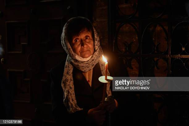 An Orthodox worshipper holds a candle during the Easter midnight mass in front of the golden-domed Alexander Nevski Cathedral in Sofia on April 18...