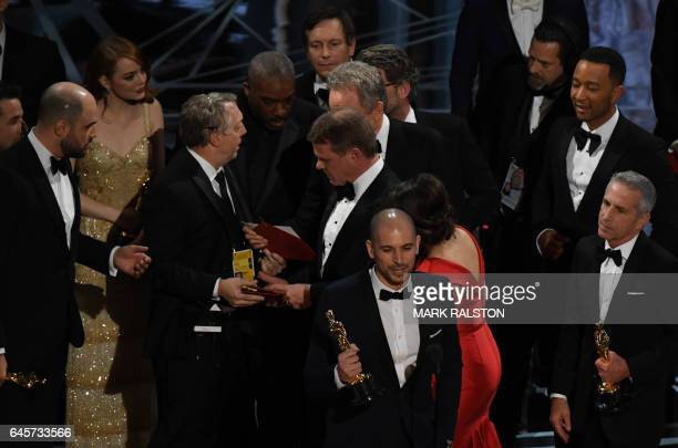 An Oscar show producer shows the winners card to the cast of La La Land after it mistakenly won the best picture instead of Moonlight at the 89th...