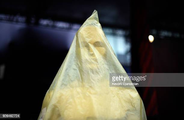 An Oscar statue is covered with plastic to protect from the rain on the red carpet during preparations for the 90th Academy Awards on March 2 2018 in...