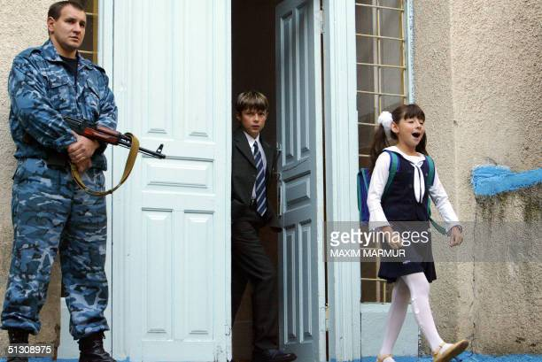 An Ossetian police officer stands guard outside school No 6 in Beslan North Ossetia 15 September 2004 as schools in the town reopened after the...