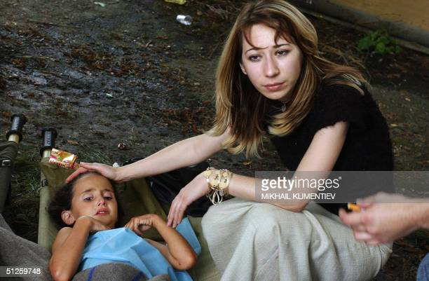 An Ossetian woman comforts a girl during the rescue operation at Beslan school North Ossetia 03 September 2004 Some 646 local residents and former...
