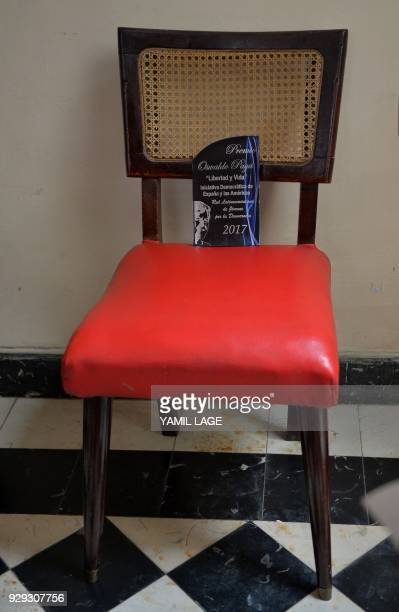 An 'Oswaldo Paya Libertad y Vida' award a prize given on behalf of the dissidence in Cuba sits on a symbolically empty chair at the house of the...