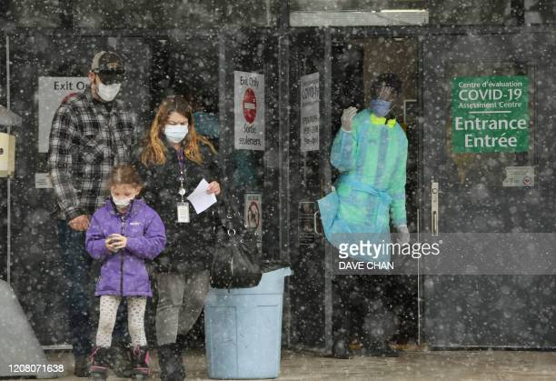 An Ottawa Public Health officer waves to the next person in line at the COVID19 testing center March 23 2020 in Ottawa Canada