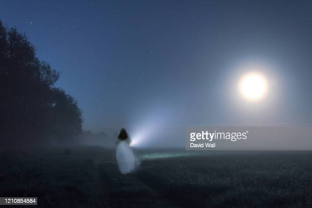 an out of focus, blurred ghostly woman wearing a white dress, carrying a torch, running away from the camera. on a misty winters night in the countryside. - white dress stock pictures, royalty-free photos & images