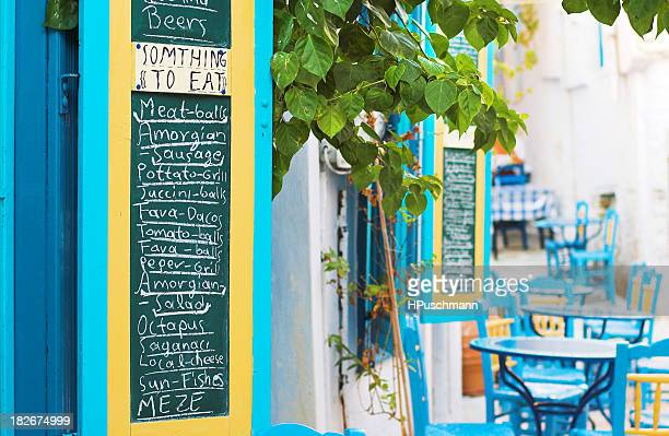 An outdoor cafe with blue chairs and menu chalkboard