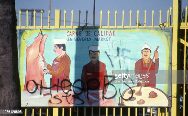 An outdoor market in Los Angeles California has an image of three men cooking a pig hanging on the fence 1999