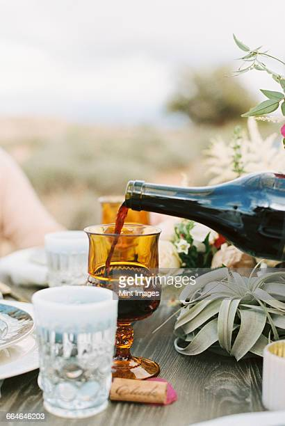 An outdoor meal, red wine being poured into a glass.