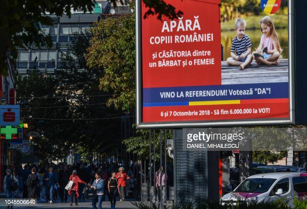 An outdoor poster reading in Romanian 'Defend the children of Romania and the marriage between a man and a woman come to the referendum and say...
