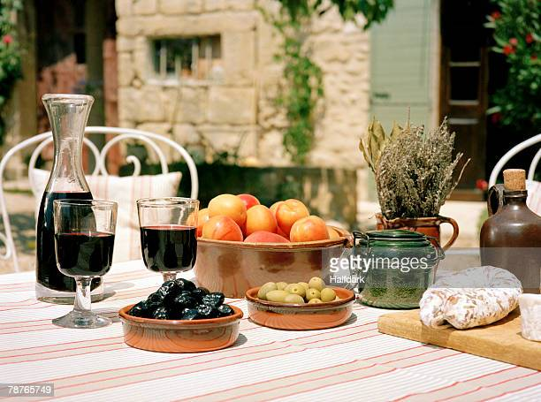An outdoor table set with wine and appetizers