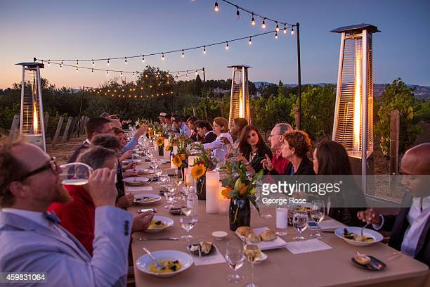 An outdoor winery dinner takes place in the middle of a pinot noir vineyard at sunset in the Russian River Valley on August 20 near Healdsburg...