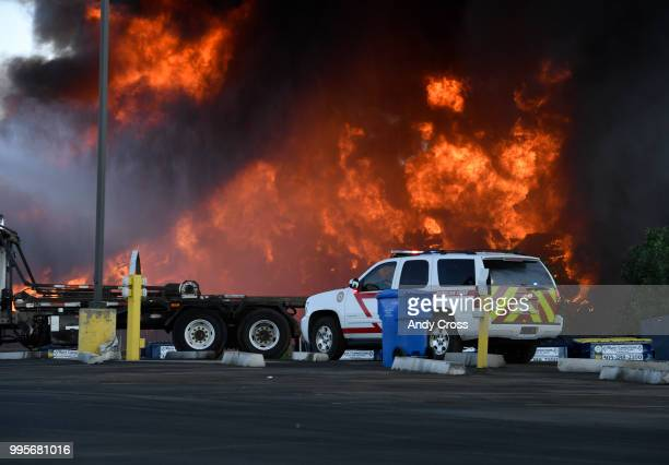 An outofcontrol fire rages from a large pile of crushed vehicles near 5600 York St July 10 2018