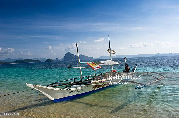 EL NIDO PALAWAN PHILIPPINES An outrigger boat at the beach of one of the many islands in El Nido archipelago El Nido is bordered by the Linapacan...