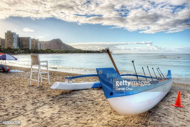 CONTENT] An Outrigger Canoe at Waikiki Beach with Diamond Head in background on a bright day in Honolulu Hawaii