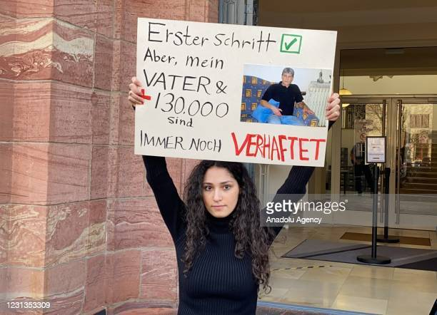 An outside view of Higher Regional Court of Koblenz, as a person whose father was reported to have been tortured hold a banner in front of the court...