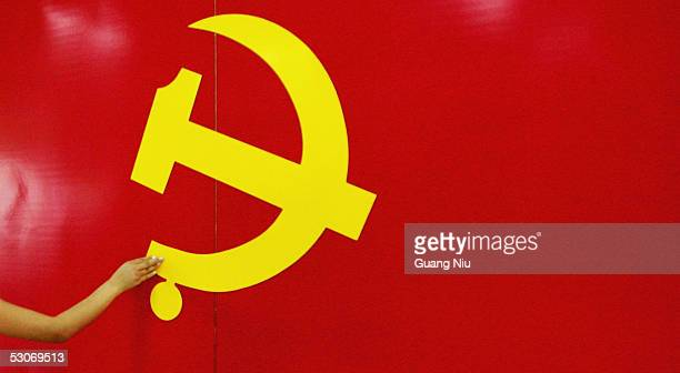 An outstrected hand touches the Hammer and Sickle logo at an exhibition promoting the Chinese Communist Party on June 15 2005 in Beijing China A...