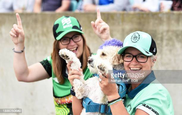 An Oval Invincibles fan watches on alongside their pet dog during the Eliminator match of The Hundred between Oval Invincibles Women and Birmingham...