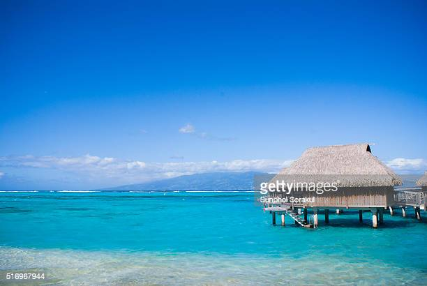 An over water bungalow on tropical island with Tahiti island and mountain background