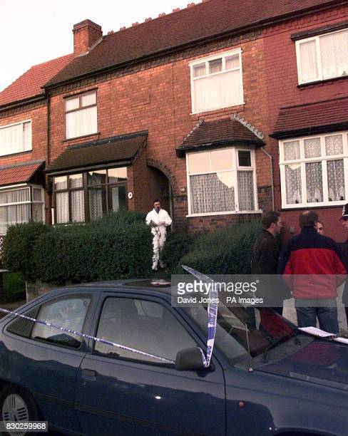 An overalled police investigator stands in the doorway of the house in Bromyard Road Sparkhill Birmingham where the bodies of three children and two...