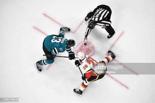 An overhead view as Barclay Goodrow of the San Jose Sharks takes a face-off against Elias Lindholm of the Calgary Flames at SAP Center on March 31,...