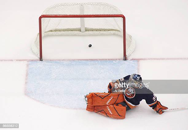 An overhead view as goaltender Rick DiPietro of the New York Islanders moves to stop the puck shot by Zach Parise of the New Jersey Devils on...