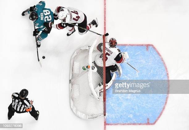 An overhead view as Timo Meier of the San Jose Sharks skates behind the net against Kevin Connauton and Darcy Kuemper of the Arizona Coyotes at SAP...