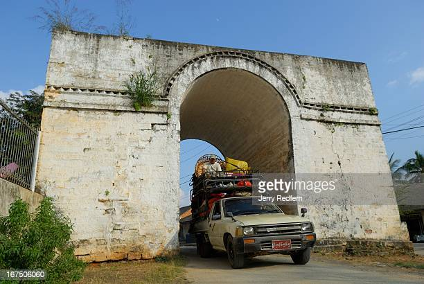 An overloaded truck passes through the White Gate all that remains of the fortified ancient wall that once encircled Kengtung Myanmar The town is an...