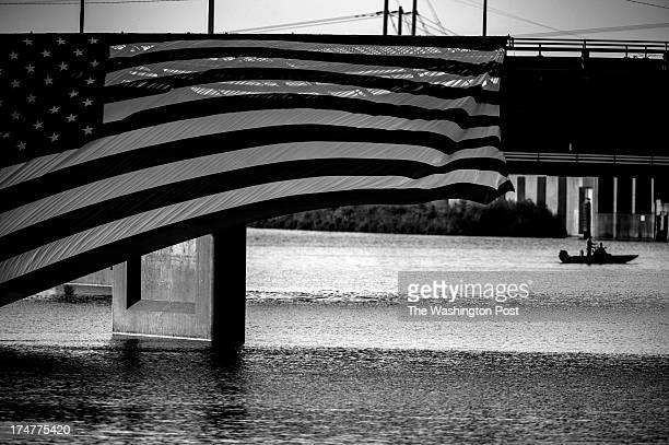 AUGUST 14 An oversized American flag flutters in the wind as members of the secret service detail patrol the Cedar River before President Barack...