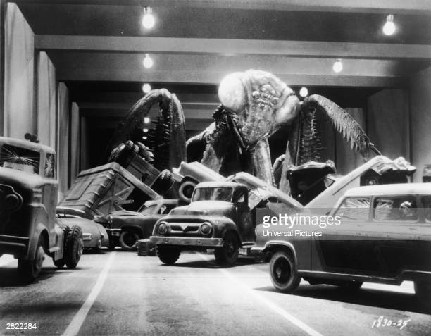 An oversized prehistoric praying mantis wreaks havoc in a freeway underpass as it overturns cars and trucks in a film still from 'The Deadly Mantis'...